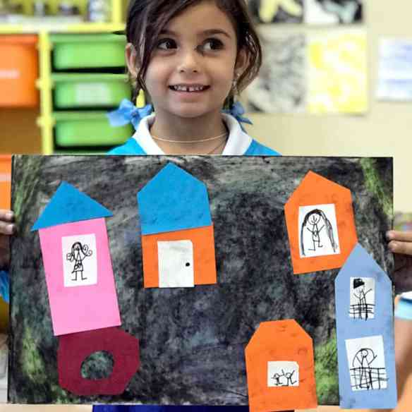 Girl holding mixed media collage of city – Paul Klee Art for Kids