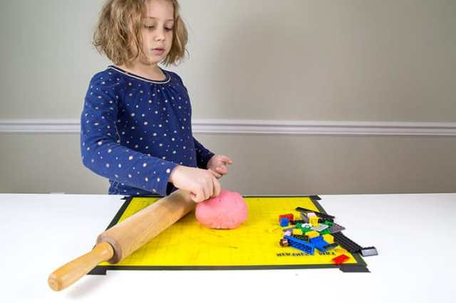 Girl standing by yellow mat with rolling pin, playdough and LEGOs