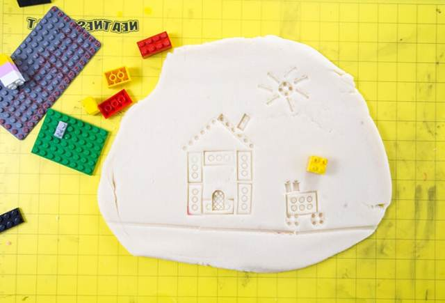 LEGO prints of house scene imprinted on playdough with LEGOs on mat