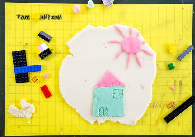 Yellow mat with playdough house & legos for LEGO prints in playdough art activity