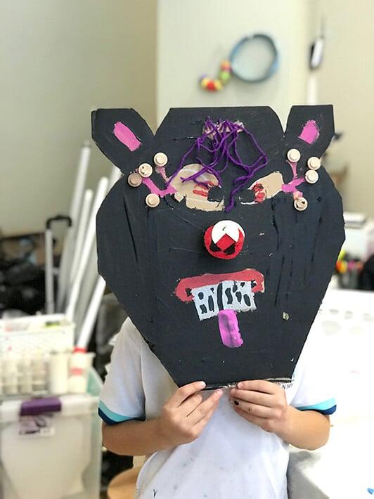 Child holding up Miró inspired black cardboard animal mask