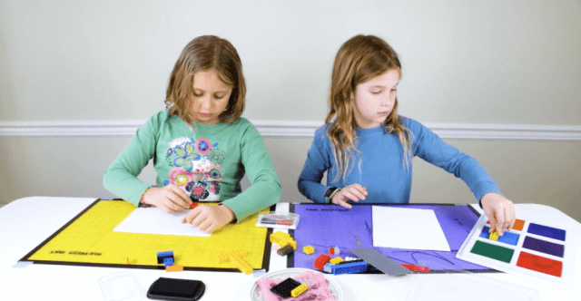 Two girls using stamp pads & LEGOs to create LEGO prints