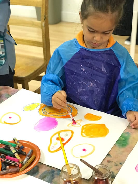 Boy painting colorful circles with watercolor paint for Yayoi Kusama Inspired Dot Paintings for Kids