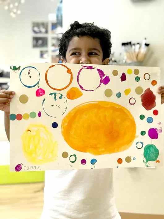Child holding up Yayoi Kusama Inspired Dot Paintings
