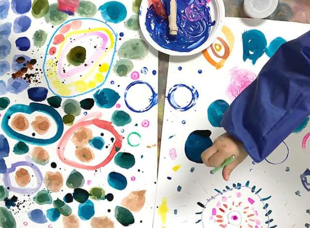 Child painting colorful circles and dots for Yayoi Kusama Inspired Dot Paintings for Kids