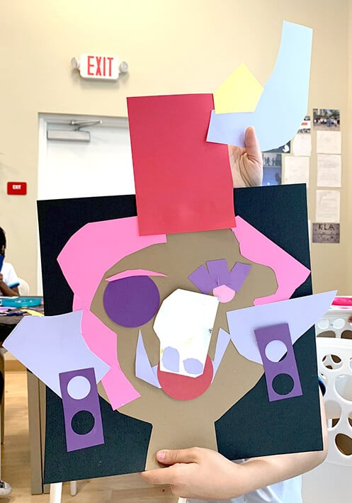 Student holds up Picasso inspired collage portrait with pink and purples cut paper shapes