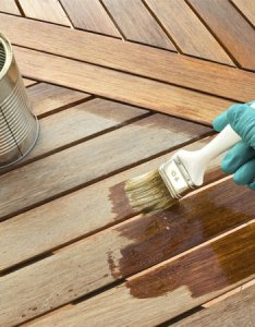 Photo of someone staining their deck with wood stain also best buying guide consumer reports rh consumerreports