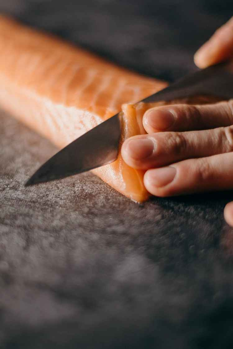 photo of person slicing salmon