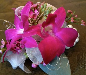 Purple orchids are attached to a pearl wrist bracelet for a lasting keepsake gift.