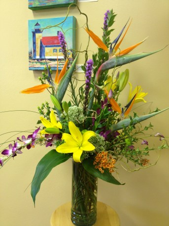 Bold and bright...tropical blooms such as birds of paradise and orchids make this a long lasting design.