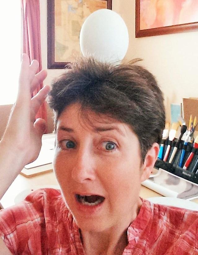 Alison Nicholls balancing an ostrich egg on her head