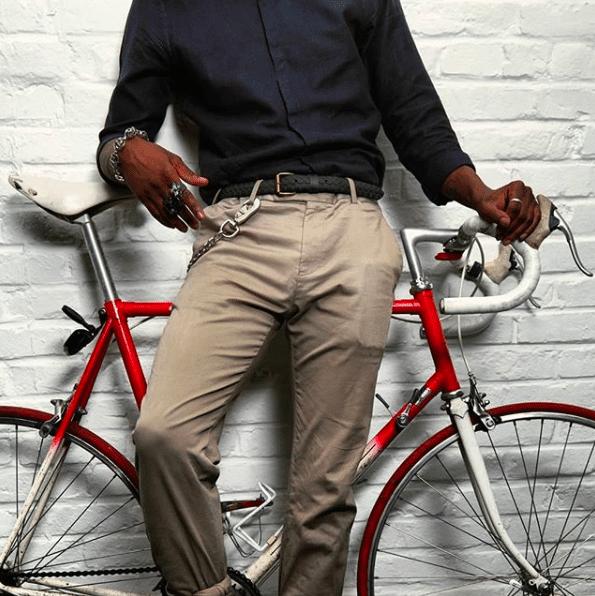 Un homme adossé sur un vélo portant une ceinture de la marque la vie est Belt