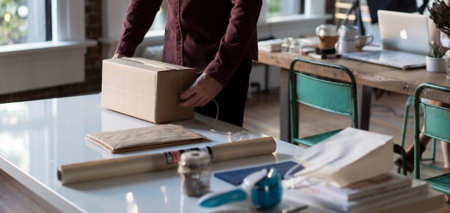 Une personne debout devant une table prépare son colis à expédier. Photo utilisée pour illustrer le fait de vendre sur etsy puis d'organiser l'expédition de son produit