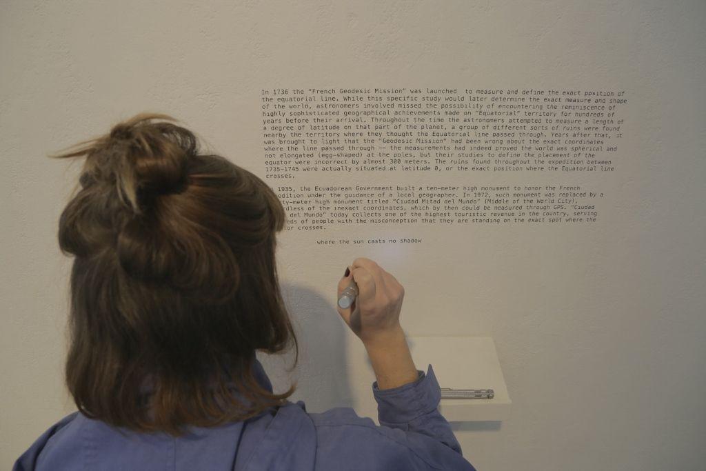 Maio Alvear, Where the Sun Casts no Shadow, texto en vinilo sobre pared, repisa y linterna