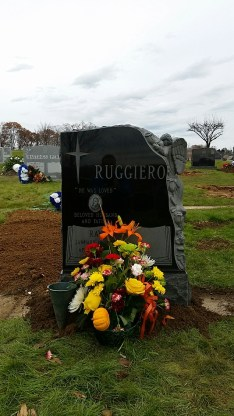 Recently completed monument with a weeping angel carved from black granite