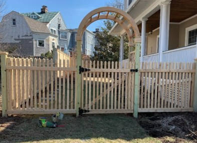 Wooden picket fence and arbor with gate leading into a backyard designed and installed by Artistic Fence company