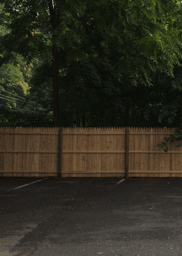 Solid wood fence in a commercial parking lot