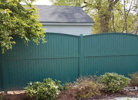 Painted wood privacy fence with crowning