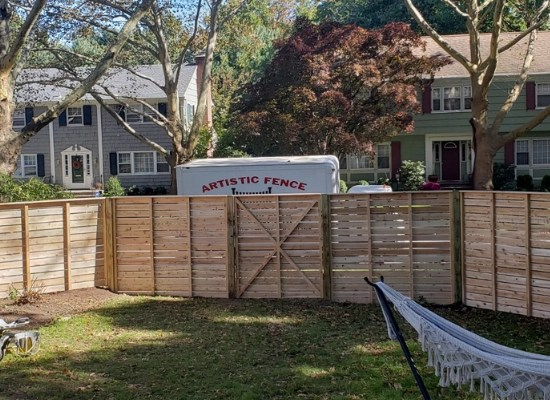 Horizontal wood fence and gate with Artistic Fence truck parked on the other side