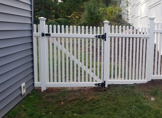 White vinyl picket fence gate with black fence hardware