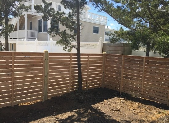 Horizontal wood fence with spacing in a backyard