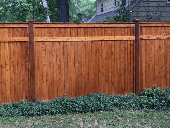 Stained wood full privacy fence built and installed by Artistic Fence Company