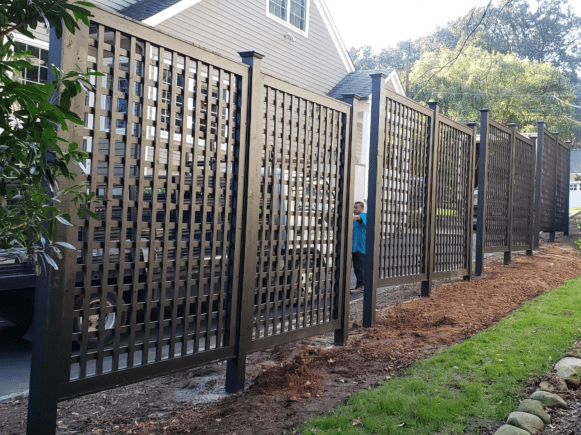 Black painted wood lattice separating two driveways