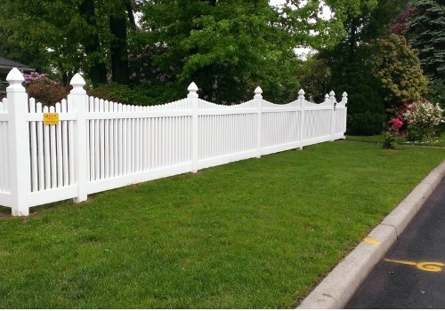 White scalloped picket fence installed in New Jersey by Artistic Fence company with yellow gas utility markout on the curb and road