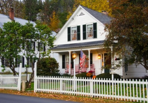 Colonial white house with front porch and white picket fence