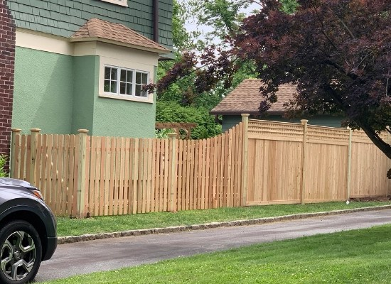 Installation of wood fence in Montclair, NJ   Artistic Fence Company style #104 picket fence scalloped into style #221 solid wood fence with square lattice