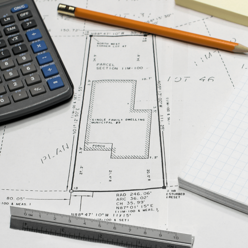 Copy of a property survey on a messy desk with a calculator, pencil and ruler
