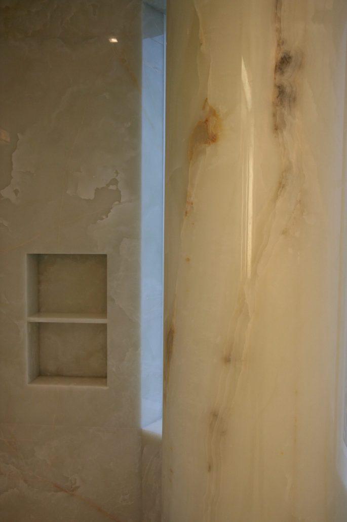 Master bathroom shower floor, walls, niche and column in white onyx