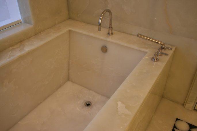 Master bathroom bathtub in white onyx slab