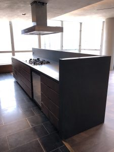 Kitchen island in black granite slab and tile floor