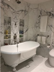 Master bathroom walls and niches in calacatta marble slab with thassos tile floor