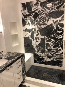 Children's bathroom shower feature wall in grand antique and white dolomiti marble slab