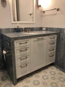 Bathroom vanity in blue quartz slab with custom mosaic floor