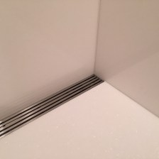 Master bathroom shower in white thassos slab with linear drain