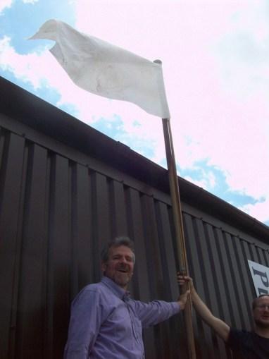 Michael Cahn and Robert Good hoist a flag