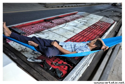 Drivers in Bangkok work very hard. They sometime need a break and use hammoc between their truck and the street to sleep