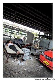 This taxi driver sleeps on a table next to his car!