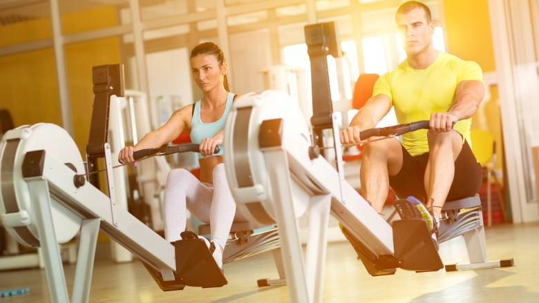 Fit  couple on row machine in gym