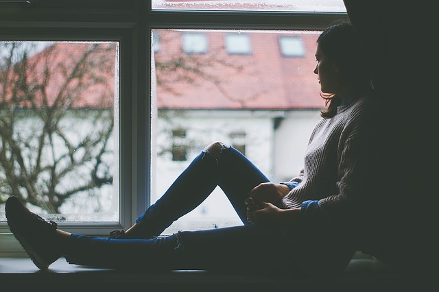 Woman sat in a window and looked out. The image is dull, very depressing and suggests that she is suffering from postnatal anxiety