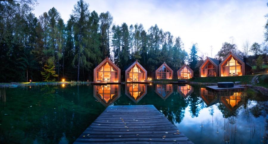 Zwanzig Chalets aus schwarzem Holz und Glas fügen sich sanft in die Landschaft. Am Waldrand, um das Hauptgebäude oder den tiefgrünen Naturteich.