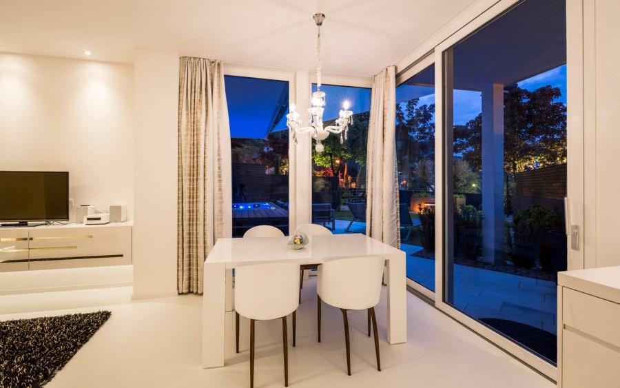 Durch großflächige Glasfenster verschmelzen Wohnraum und Natur.