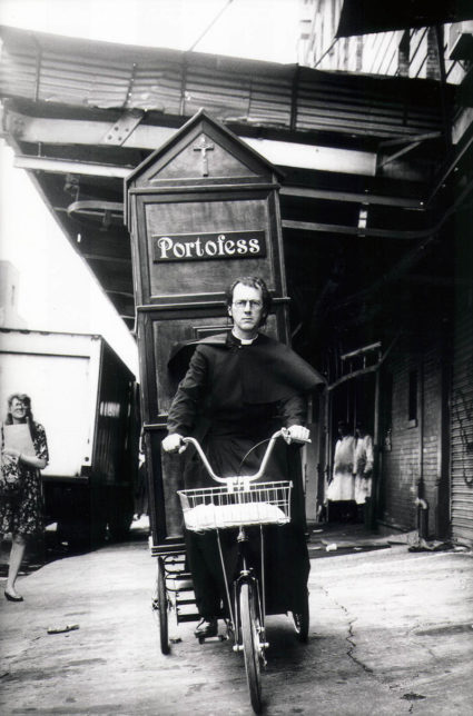 Father Anthony Joseph (aka Joey Skaggs) pedals his Portofess to the 1992 Democratic National Convention, courtesy Joey Skaggs Archive
