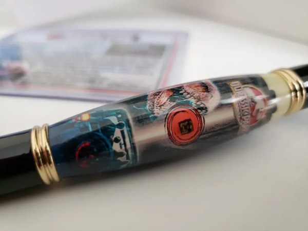 Jurassic Park movie history memorabilia pen with authentic wood from the movie cast in acrylic wrapped in Jurassic Park graphic