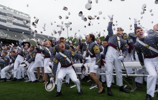 Image of West Point graduates throwing their caps in the air