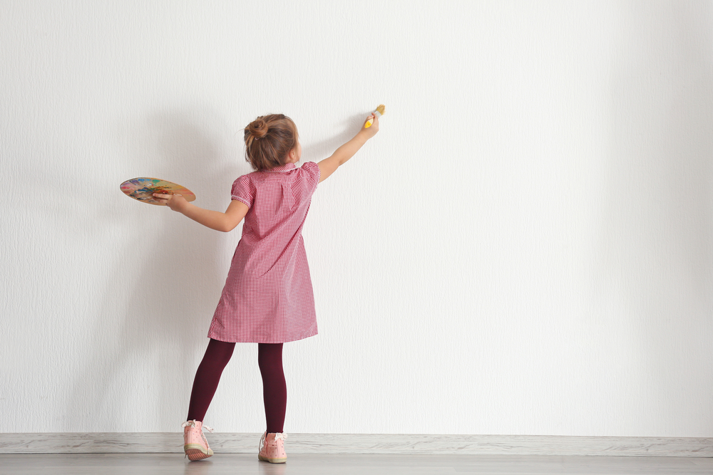 Image of a girl just starting to paint a blank wall