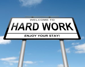 Road sign that says: Welcome to Hard Work-Enjoy Your Stay